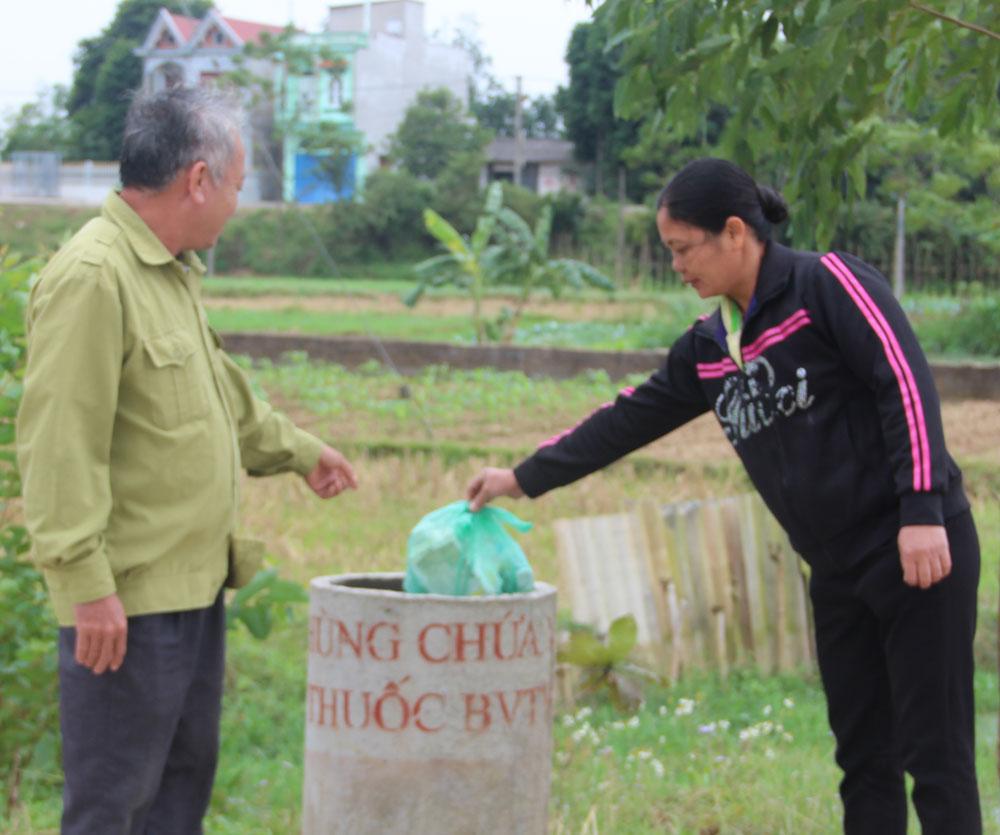 Nông dân thôn 5, xã Nghĩa Hưng bỏ vỏ thuốc bảo vệ thực vật vào thùng chứa.