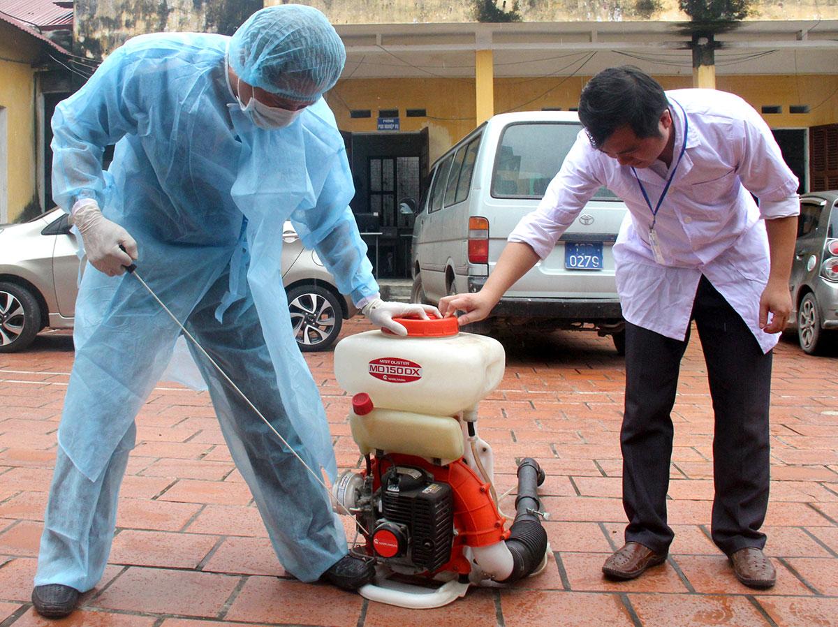 Nhân viên Trung tâm Y tế huyện Hiệp Hòa chuẩn bị máy móc phun hóa chất diệt muỗi phòng bệnh sốt xuất huyết cho các hộ dân trên địa bàn.