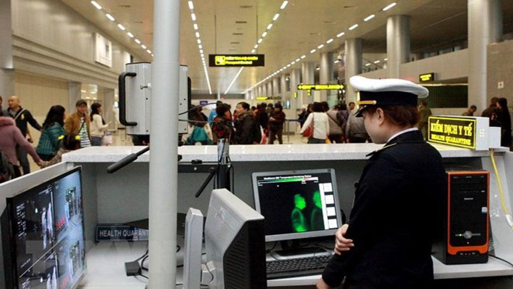 Nhân viên Trung tâm Kiểm dịch Y tế quốc tế kiểm tra thân nhiệt và kê tờ khai y tế cho hành khách. (Ảnh: Dương Ngọc/TTXVN)