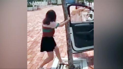 Hai cô gái luống cuống khi cửa ôtô bị vướng vào thân cây