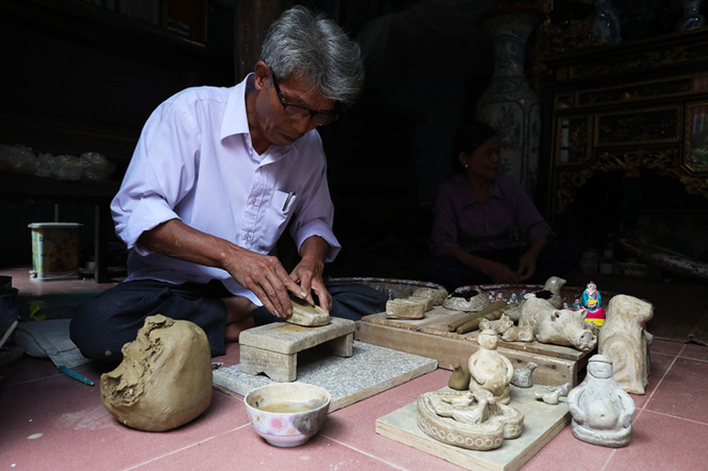 Artisan, legacy of clay statue making, northern Vietnam, Phung Dinh Giap, Bac Ninh province,  craftspeople, once-popular traditional figurines, traditional clothes