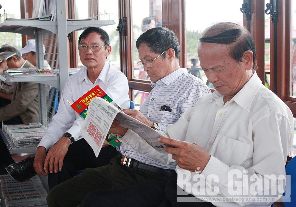 Người cao tuổi đọc báo tại Nhà sinh hoạt cộng đồng ở Khu vui chơi Người cao tuổi.