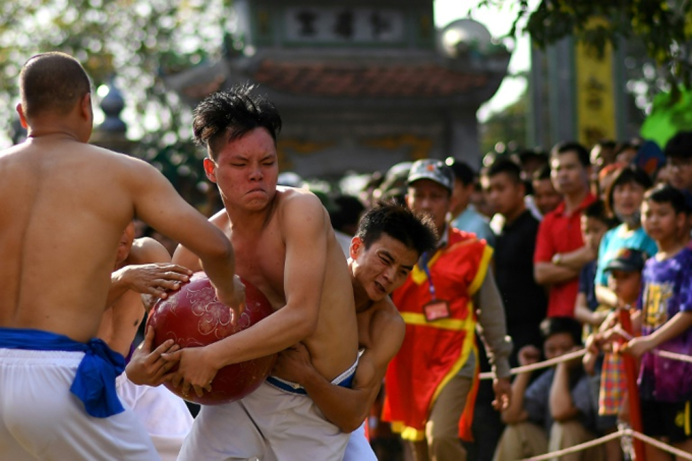Wrestling for glory, Vietnam, 'Vat Cau' festival, Bare-chested men,  brightly colored belts, excited spectators, centuries-old sport, three-day annual festival, Lunar New Year