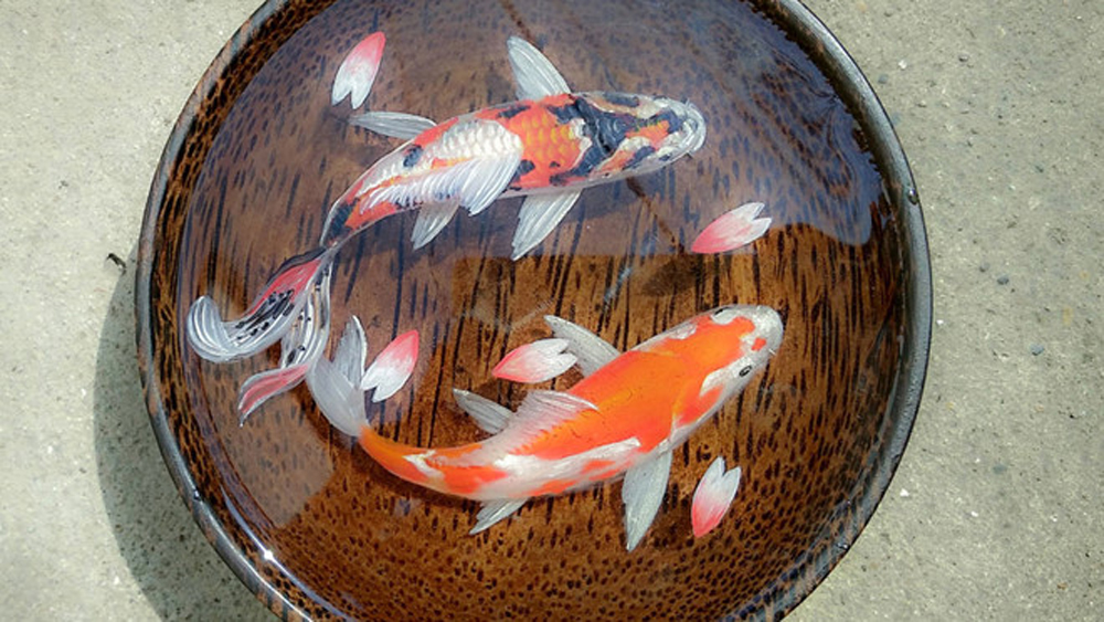 A Saigon artist paints fish with an additional dimension
