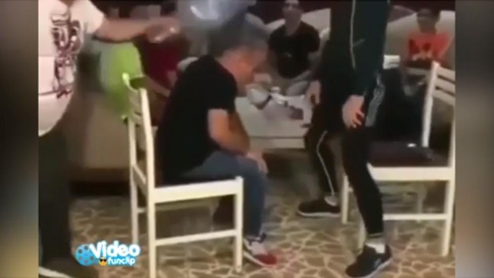 Người đàn ông no đòn khi chơi trò đập chai nước vào đầu