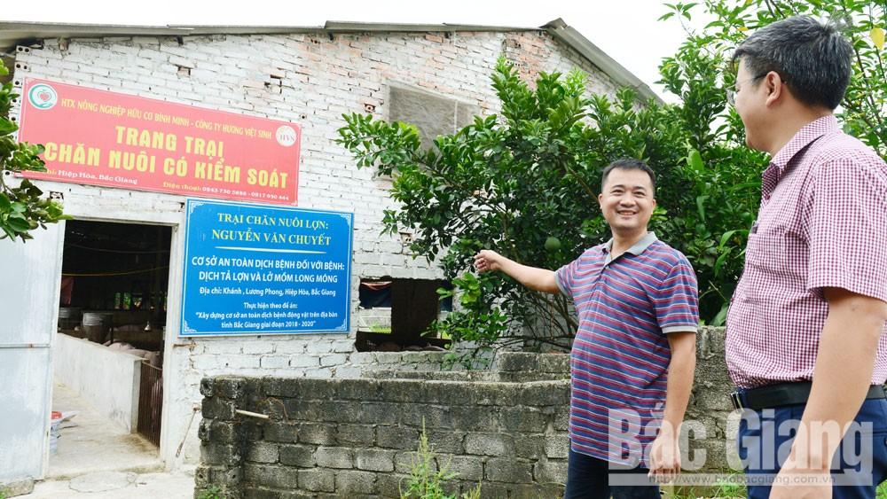Ông Nguyễn Ngọc Hải (bên trái), Giám đốc HTX Nông nghiệp hữu cơ Bình Minh (Hiệp Hòa) giới thiệu cơ sở chăn nuôi an toàn dịch bệnh.