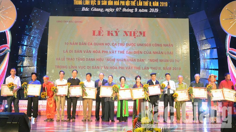 Thừa ủy quyền của Chủ tịch nước, đồng chí Nguyễn Văn Linh và đồng chí Đỗ Đức Hà trao danh hiệu Nghệ nhân Ưu tú cho các nghệ nhân.
