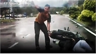 Áo mưa quấn vào bánh xe quật cô gái ngã ngay trước đầu ô tô