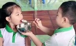Cậu bé ga lăng bón cơm cho bạn gái