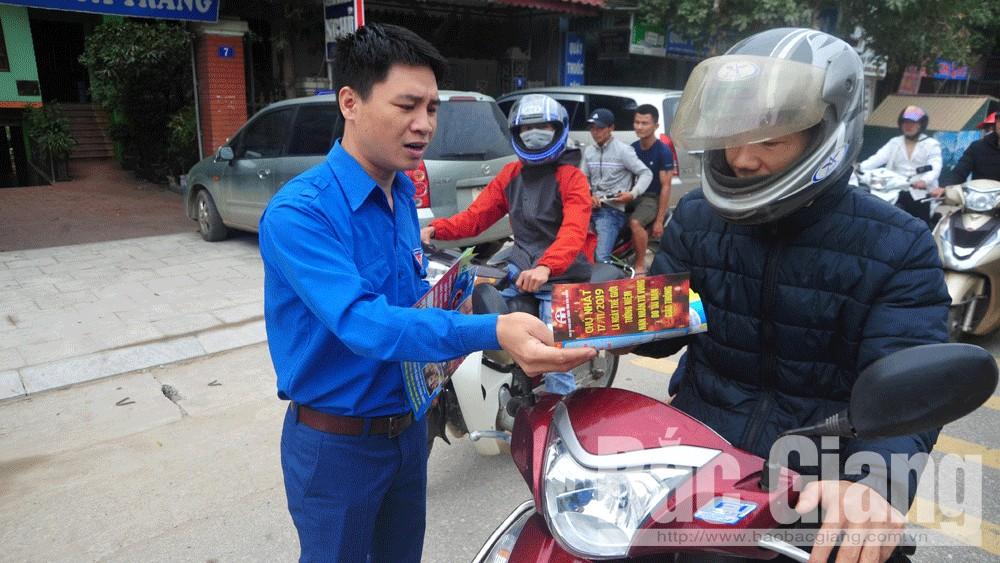 Tình nguyện viên phát tờ rơi tuyên truyền về ATGT tại điểm tưởng niệm ngã tư Đình Trám (Việt Yên).
