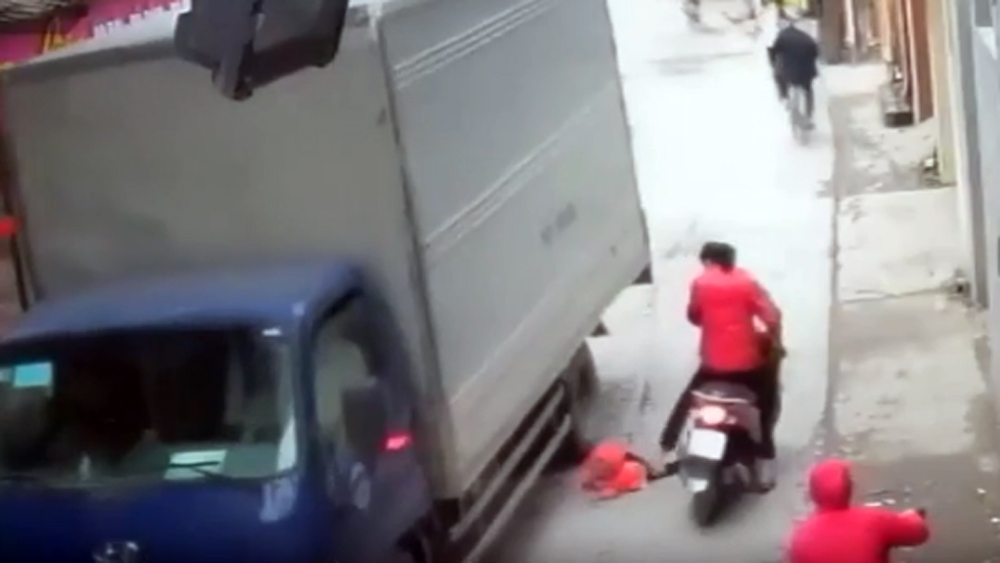 Hà Nội: Cháu bé ngã từ xe máy xuống đường suýt bị xe tải cán