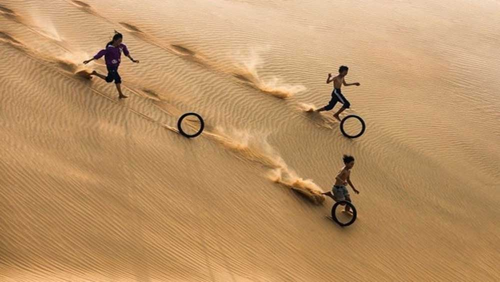 Photo of Vietnamese children, Agora app contest, overall winner, World's Best Photo of Fun,  old motorcycle tyres, sand dune, fishing town of Mui Ne