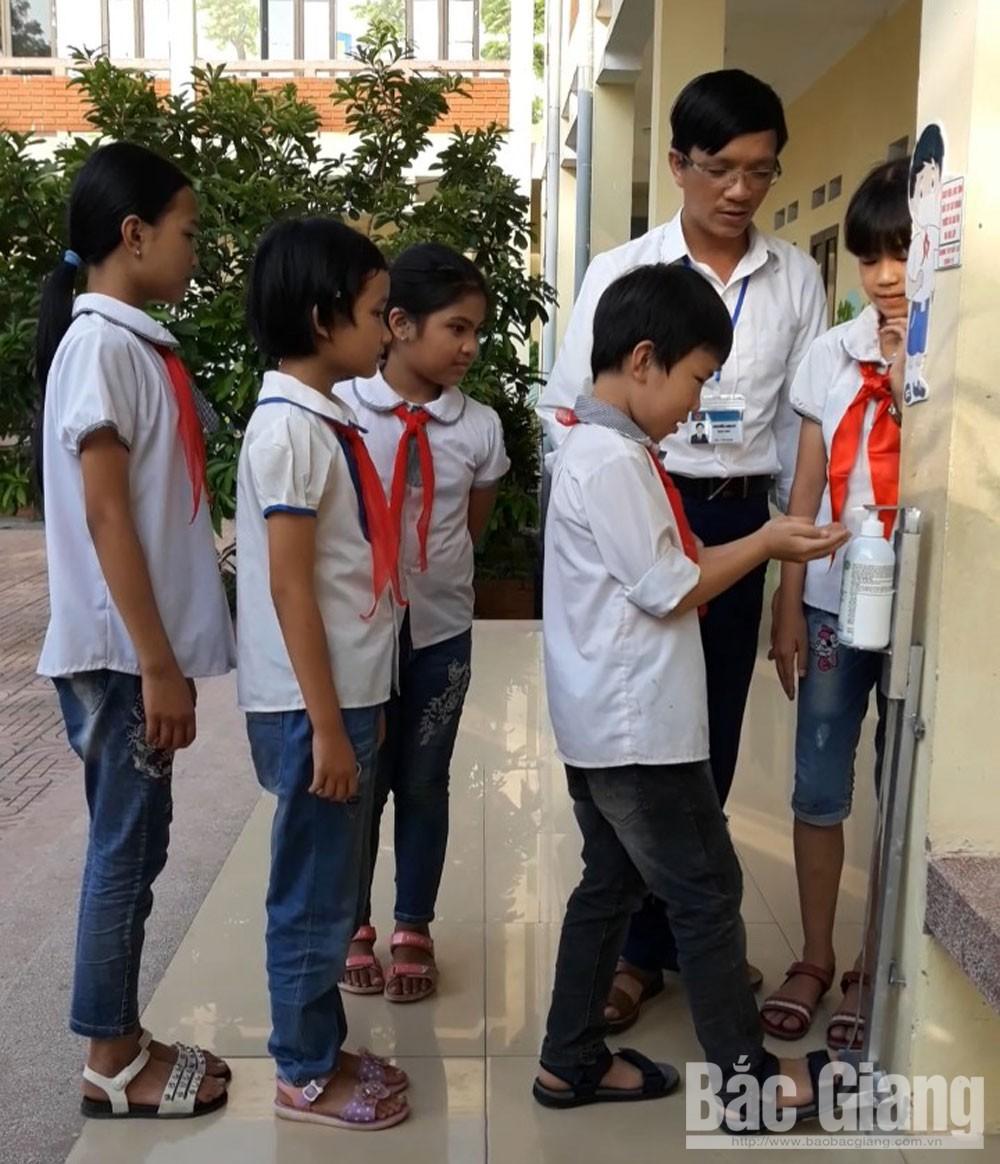 Thầy Tú hướng dẫn học sinh sử dụng thiết bị khi rửa tay sát khuẩn.