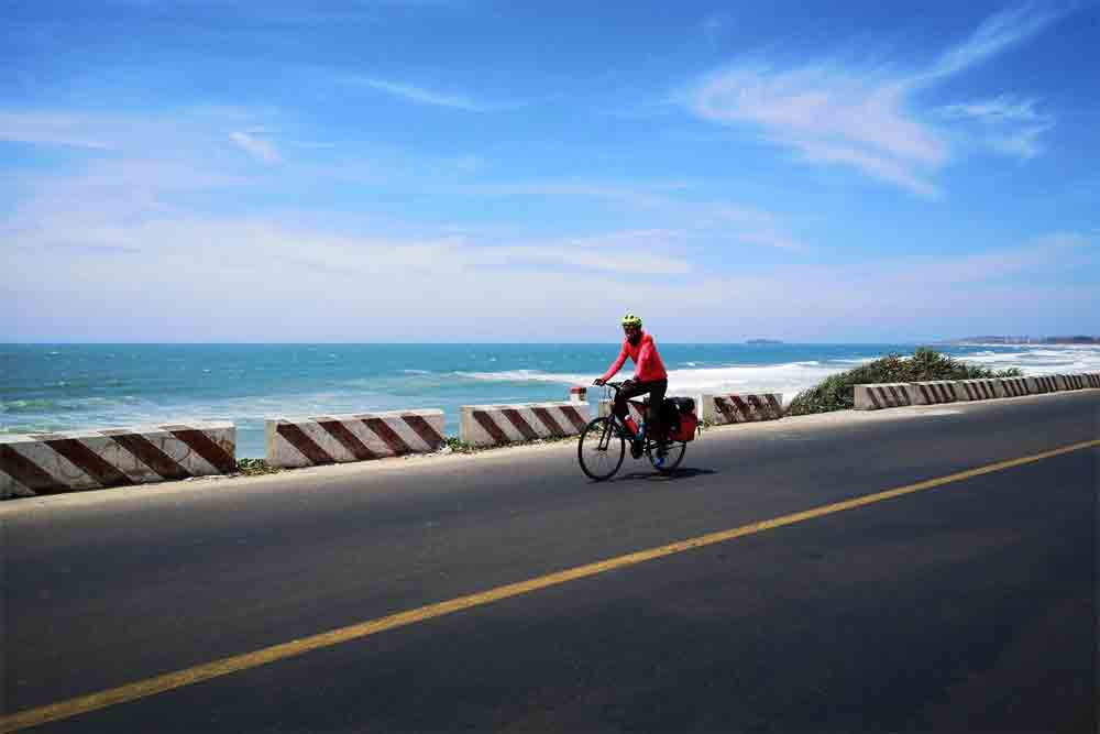 South central Vietnam, group of cyclists, beautiful landscapes, bougainvillea bushes, beach area, 11-day trip, strong headwind, popular coastal town, best paradise islands