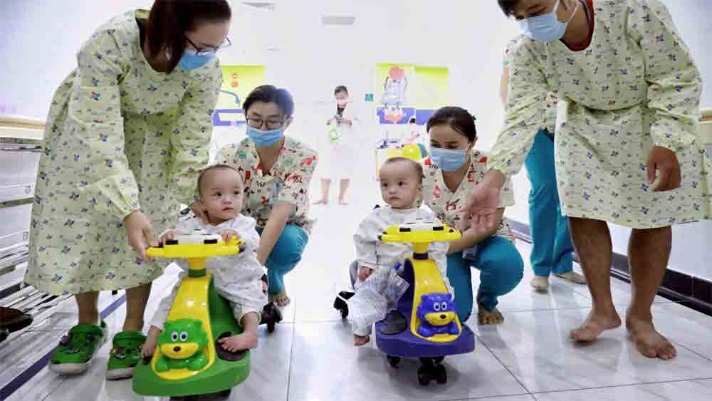 Saigonese conjoined twins, embrace split life, Truc Nhi, Dieu Nhi, learning to stand, daily physical therapy, 14 months old,