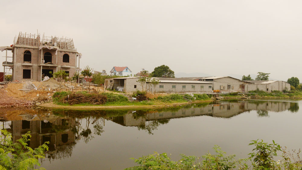 Ngôi nhà đang xây và khu chuồng trại chăn nuôi của hộ anh Tuyên.