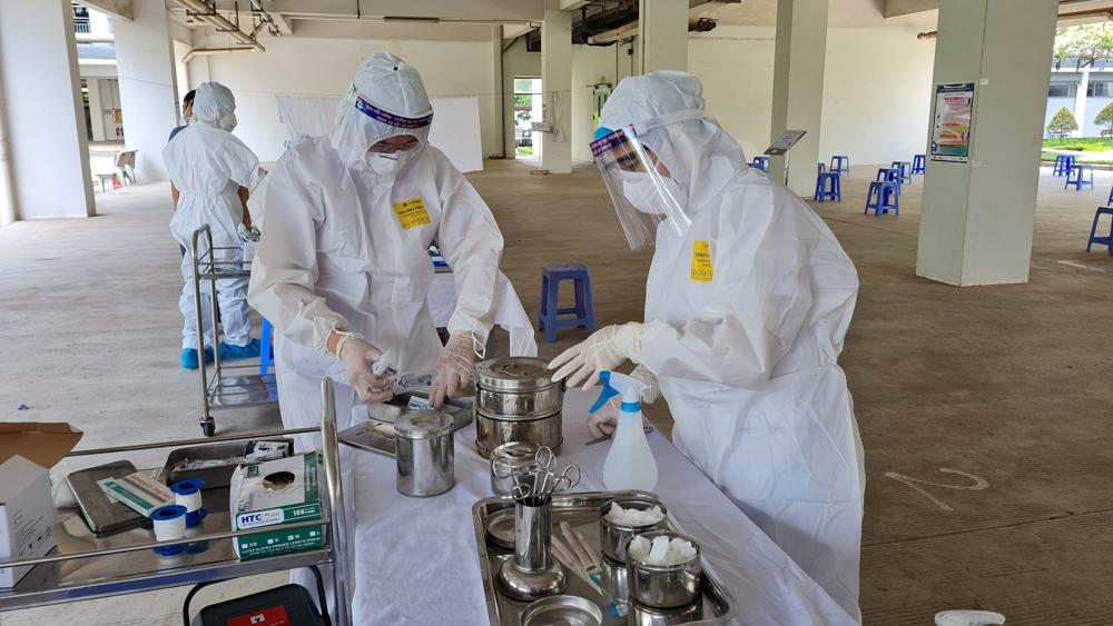 Các nhân viên y tế chuẩn bị dụng cụ để tiêm phòng Covid-19 cho công nhân tại Công ty TNHH FUHONG (KCN Đình Trám, Việt Yên). Ảnh Kim Hiếu.