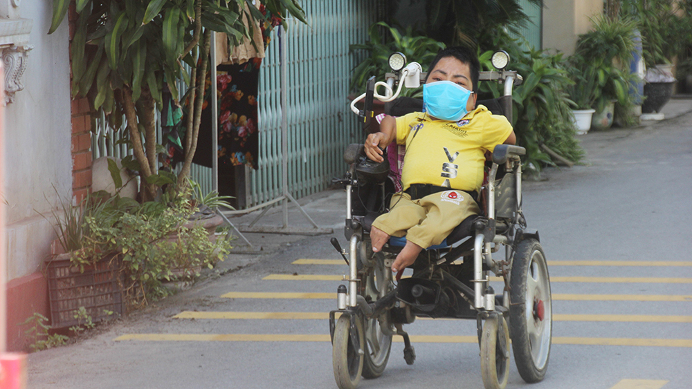 Ngồi xe lăn đi quyên góp chống dịch