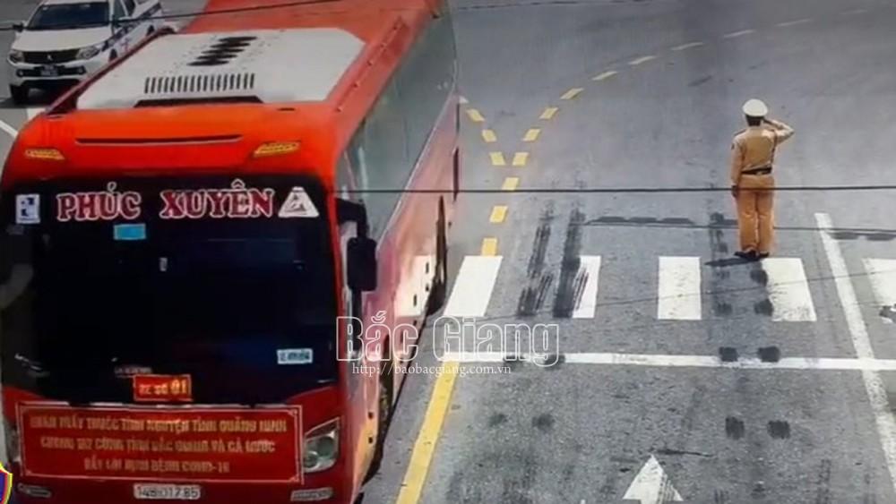 Chiến sĩ cảnh sát giao thông Công an huyện Yên Dũng đứng nghiêm, giơ tay chào đoàn xe chở cán bộ y tế tỉnh Quảng Ninh chi viện cho Bắc Giang chống dịch.